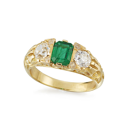 A Victorian style, emerald and diamond three stone ring, the central rectangular-cut emerald with old-brilliant-cut diamond shoulders, approximate weight of each diamond 0.35 carats, to carved gallery and shoulders, ring size M1/2