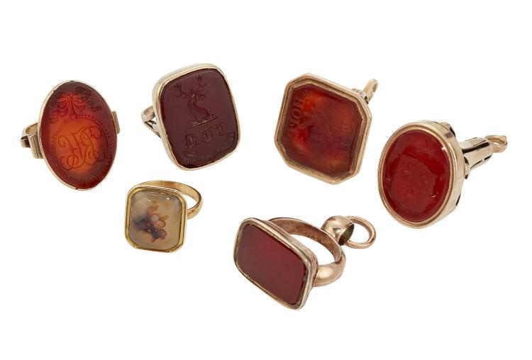 A group of late 18th and early 19th century cornelian fob seals and rings, comprising: an 18th century gold trumpet shaped fob seal with cornelian oval matrix engraved with an armorial; another of trumpet shape with octagonal seal matrix with engraved with Masonic symbols; a stirrup shaped fob seal with vacant seal matrix; a ring with engraved crest and initials; an oval seal ring engraved with initials and bow motif; and a moss agate ring (6)