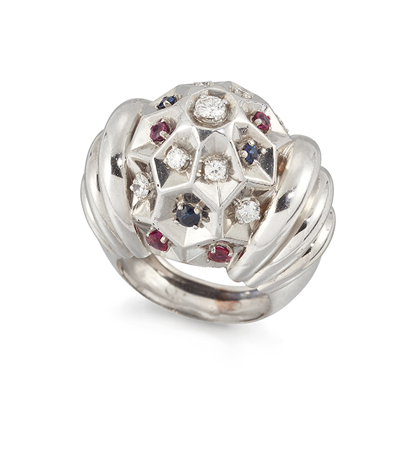 A French, platinum, diamond ruby and sapphire ring, of bombe cluster design, the central bezel of honeycomb design set with circular-cut diamonds, sapphires and rubies, to graduated ribbed shoulders, circa 1950, French assay marks, ring size K