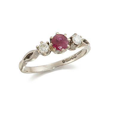 An 18ct. gold, ruby and diamond three stone ring, the central circular-cut ruby with circular-cut diamond single stone shoulders, rings size J1/2