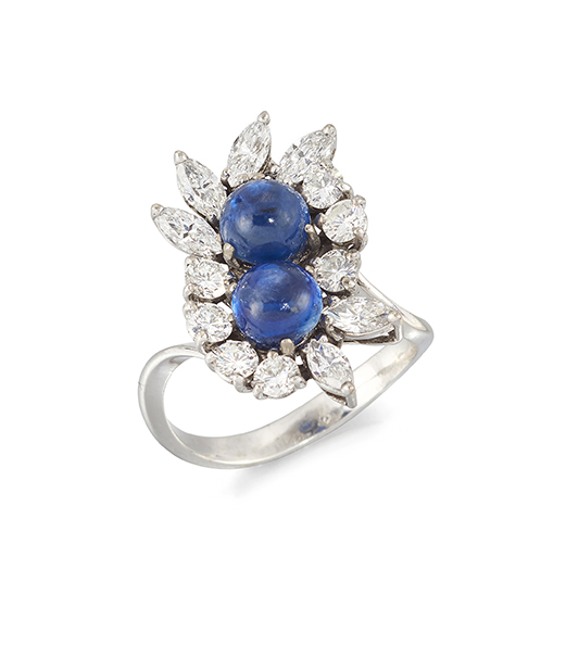 A cabochon sapphire two stone and diamond cluster ring, the two claw-set cabochon sapphires with marquise-cut diamond border to a crossover design hoop, French assay marks, ring size M