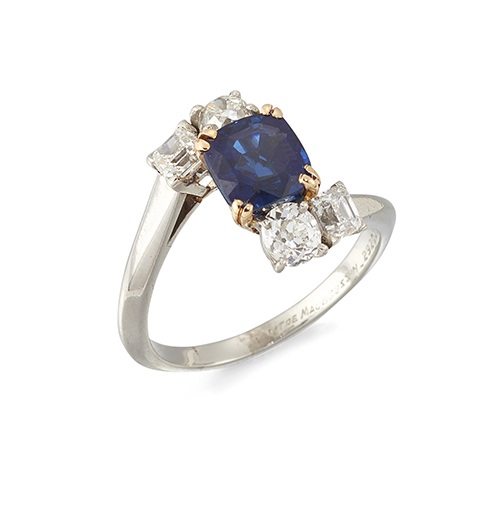 A sapphire and diamond ring mounted by Mauboussin, the square-cut cornered sapphire weighing 2.54 carats, in claw-set crossover mount with opposing old-brilliant and princess-cut diamond two stone shoulders, signed MTRE Mauboussin and numbered 29209, ring size R (Vendor states that a verbal opinion of the sapphire from the SSEF laboratory in Switzerland found no evidence of heat treatment)