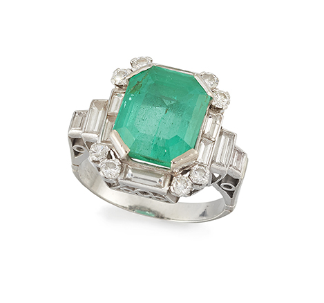An emerald and diamond ring, the rectangular-cut cornered emerald weighing approximately 4.15 carats, with baguette and circular-cut diamond border to baguette diamond four stone graduated shoulders, pierced gallery and ridged hoop, ring size I