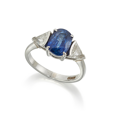 A platinum, sapphire and diamond three stone ring, the central oval claw-set sapphire weighing approximately 2.40 carats, with triangular-cut diamond single stone shoulders each weighing approximately 0.50 carats, to a plain hoop, ring size N