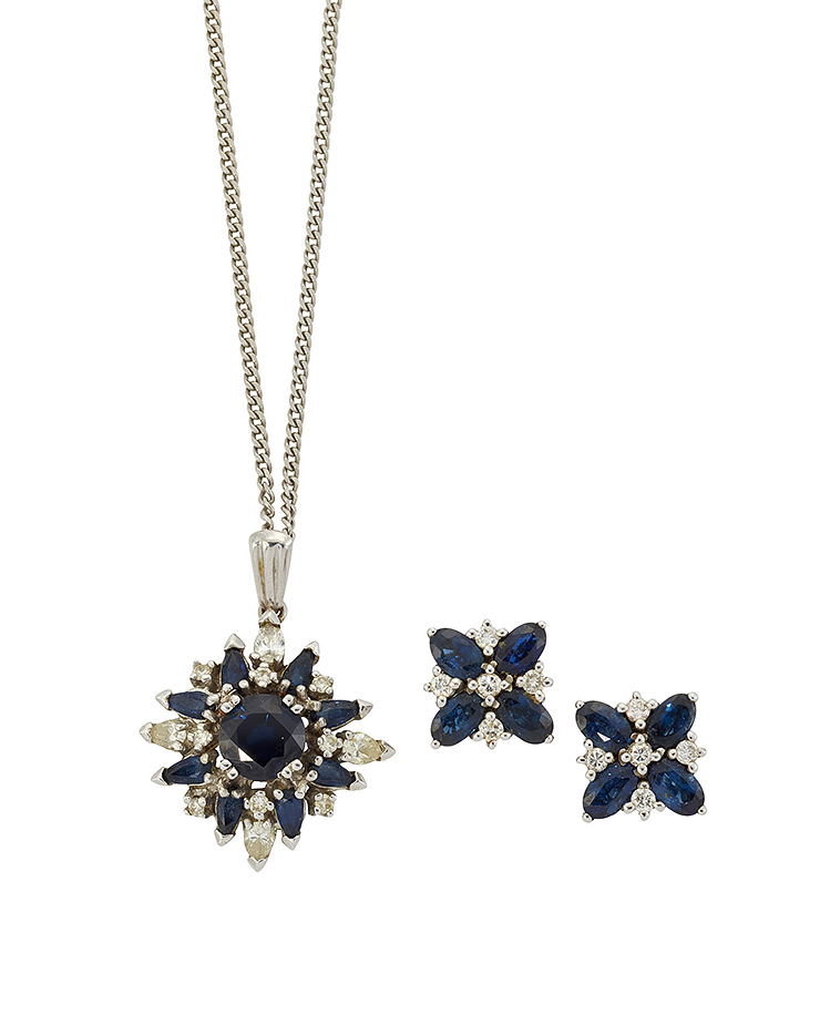 A diamond and sapphire pendant and earrings, the pendant in the form of a star shaped cluster with central claw-set circular-cut sapphire and pear-cut diamond and sapphire border and sapphire accents, to a fine curb-link neckchain, pendant 28mm, and a pair of sapphire and diamond quatrefoil design cluster ear studs (3)