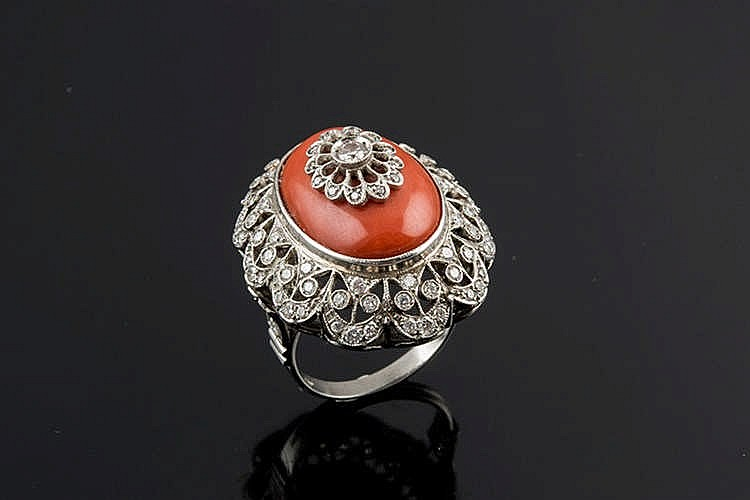 A PLATINUM, CORAL AND DIAMOND RING