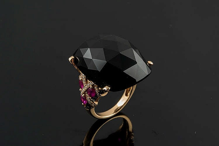 A GOLD, ONYX, RUBY AND DIAMOND RING