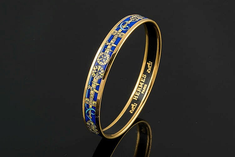 A GILT METAL AND ENAMEL, BY HERMES