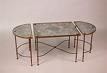 Table basse à structure en métal ciselé doré et plateaux de verre églomisé. Elle comprend un module central rectangulaire et deux latéraux semi-circulaires. Pieds cannelés réunis par une barre d'entretoise.