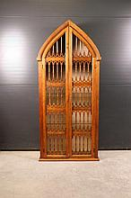 Petite bibliothèque de forme ogivale en bois exotique teinté, ouvrant à deux portes ajourées à barreaux.