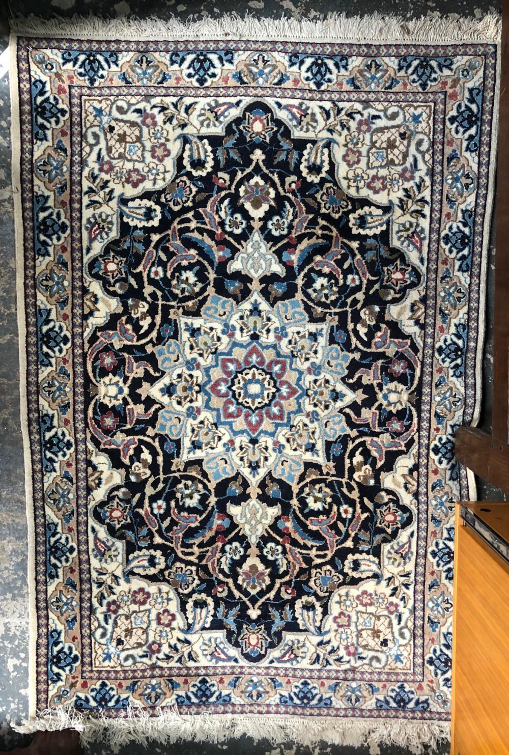 A Persian Nain rug, the traditional geometric centre medallion design in blues on ivory ground