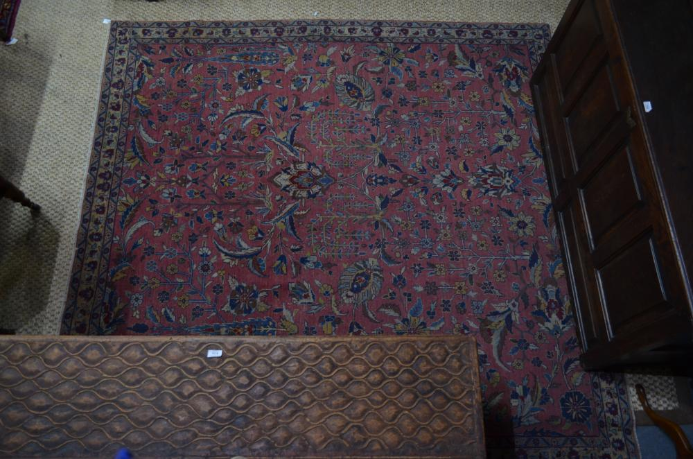 An antique Persian sarouk carpet, the overall floral design on salmon red ground