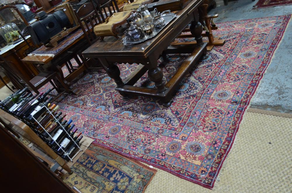 A large old Persian Kirman carpet, the repeating floral lozenge design on camel ground