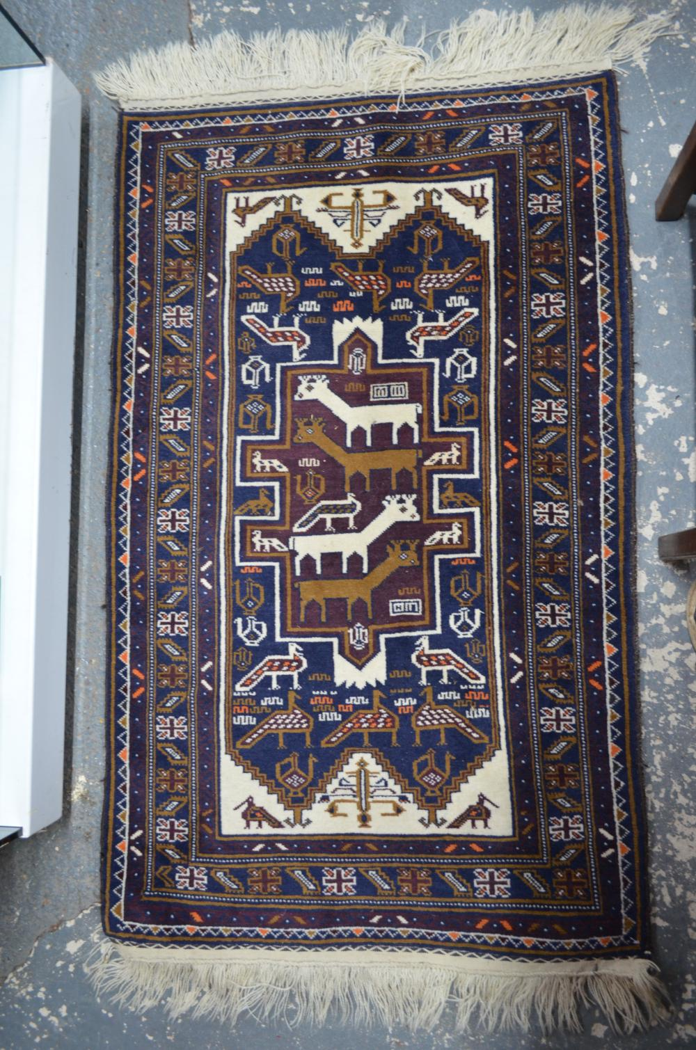 A Persian Balouch rug, the navy field decorated with various stylised animals
