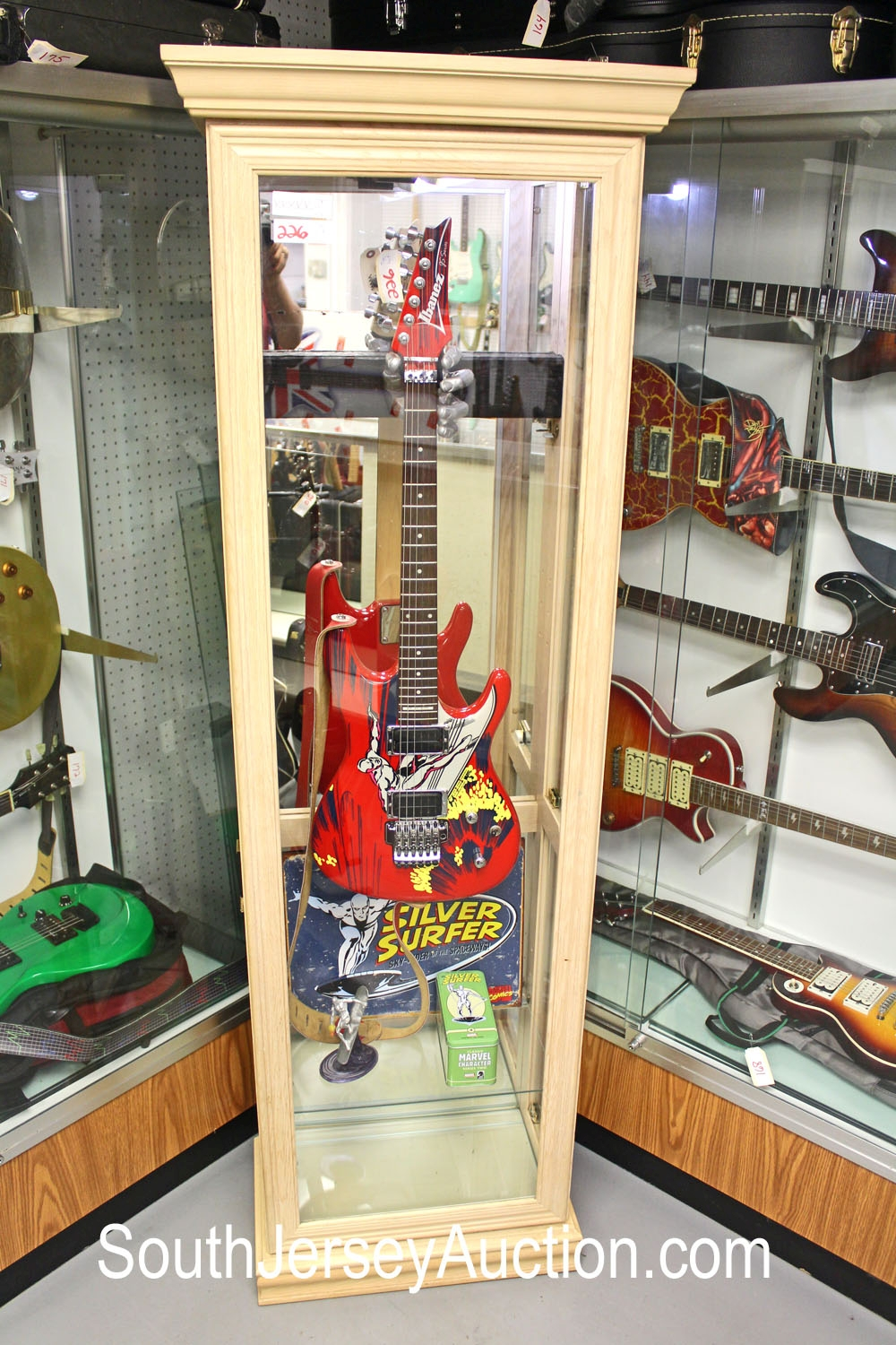 20th Anniversary Joe Satriani 'Surfing with the Alien' and all the case candy guitar and a custom-made wood and glass floor model display case with Silver Surfer metal advertisement guitar holder hand, with state and memorabilia (5 piece lot)