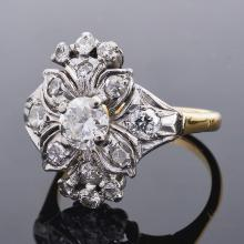 A 1940's diamond set fancy floral cluster cocktail ring the central diamond approximately 0.50ct and within a detailed outward foliate and floral diamond setting, yellow and white mount marked for 18ct and platinum