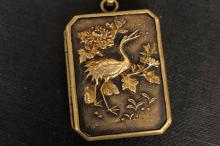 Shokudo locket set with a bird on one side and a fan on the other side, mea