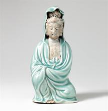 Figur der Kwan-Yin, China, 19. Jh. Knieend, in seladonfarbenem Mantel, die Hände verborgen. Kopf, Brust und Fuss aus Biscuit-Porzellan. Rückseitig Brandfehler.    H = 25,5 cm.