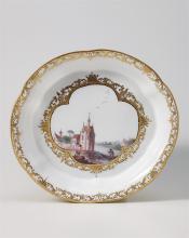 Löffelschale, Meissen, um 1740. Ovoid, mit flachem Spiegel und aufgebogenem, passigem Rand mit Goldspitzen. Bunte vierpassige, von Goldschnörkeln mit brauner Zeichnung umrahmte Reserve, darin eine...