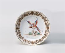 Teller, Meissen, um 1740/1750. Gemuldeter Spiegel, schräge Fahne, stark fassonierter, aufgebogener Rand mit Goldstreifen. Papageiendekor: Auf der Stange mit einem Napf mit Kirschen der krächzende...
