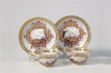 Ein Paar Koppchen mit Untertellern, Meissen, um 1730. Bunt gemalte Kauffahrteiszenen mit Arbeitern, die Schiffe beladen, mit verhandelnden Kaufleuten, mit diskutierenden Matrosen in Goldkartuschen aus...