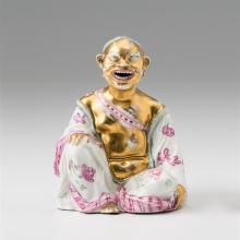 Böttger-Pagode, Meissen, um 1715. Sitzender Chinese, ein Bein aufgestützt und der rechte Arm auf das Knie gelegt, mit breitem Lachen. Körper und Kopf sind goldbemalt, er trägt eine lindengrüne...