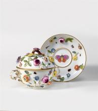 Deckelschüsselchen auf Présentoir, Meissen, um 1740/1750. Halbkugeliges Gefäss auf Standring. Seitlich je ein fassonierter, vergoldeter Doppel-C-Henkel. Bombierter Deckel mit aufgelegtem Ästchen...