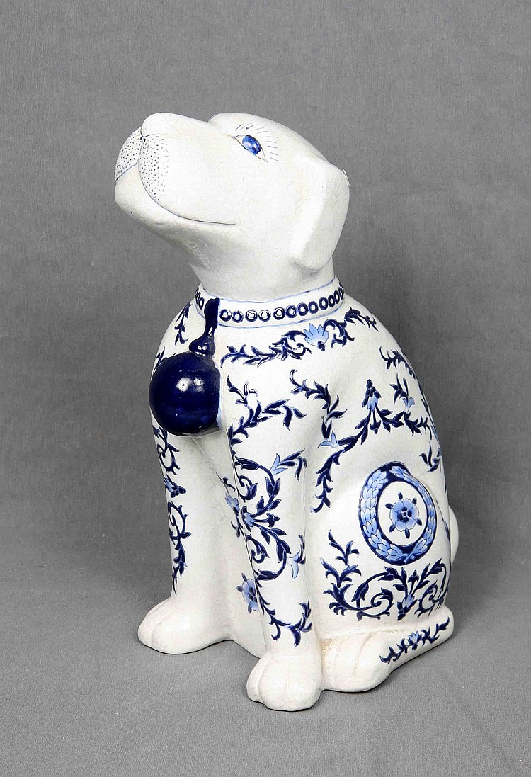 A CHINESE WHITE PORCELAIN SITTING DOG FIGURE