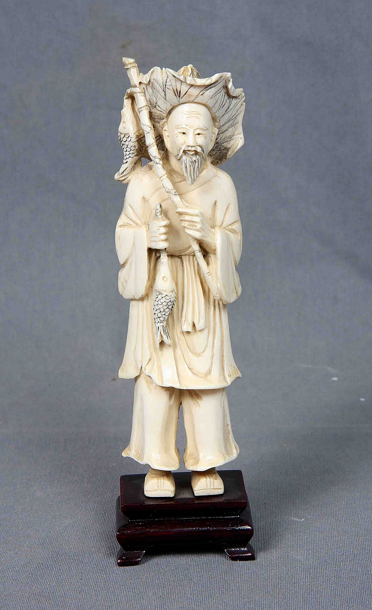 AN ORIENTAL CARVED AND POLYCHROME IVORY FISHERMAN FIGURE