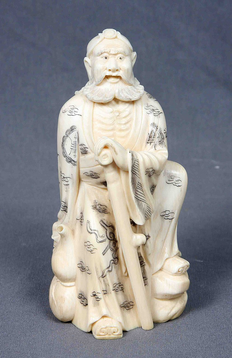 A CARVED AND POLYCHROME IVORY FIGURE