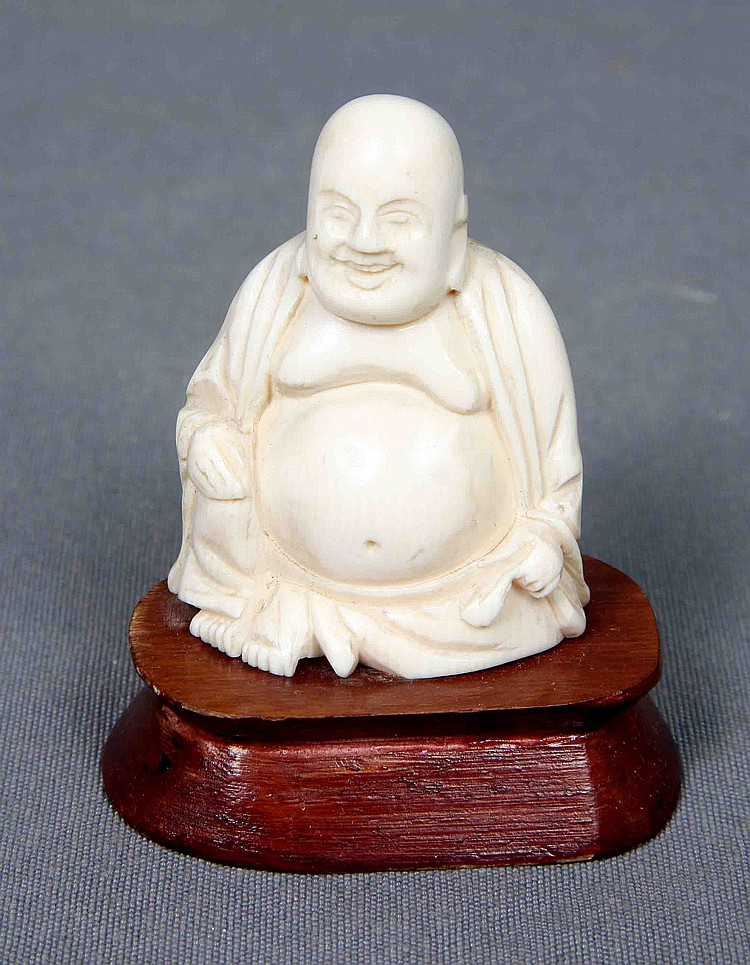 A CARVED IVORY BUDDHA FIGURE