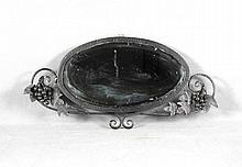 Espejo oval en hierro forjado, decorado con racimos de uvas. Med.: 38,5x80 cm.