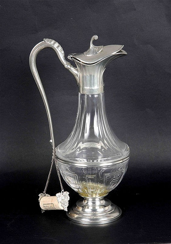 Carved glass jar, with foot, handle and tin nozzle. Seal on the base. Height: 31 cm.