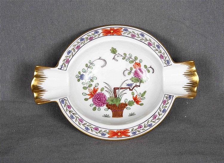 Ashtray in European porcelain, polychrome and decorated with floral motifs and gold edge. Markings and numbering at the base. Size: 14x9.5 cm.