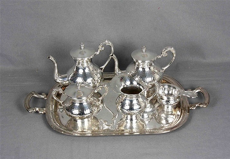 Coffee and tea set in alpaca with hammered decoration. Formed by coffee maker, teapot, milk jug, sugar bowl, colander and tray. Coffee pot height: 18 cm.