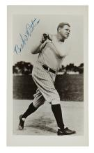 RUTH, BABE. Photograph postcard Signed, full-length portrait, showing him in uniform after swinging his bat.