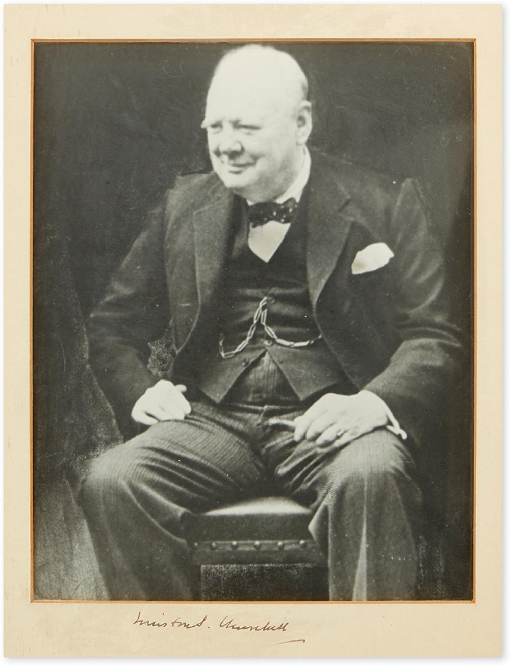 CHURCHILL, WINSTON S. Photograph Signed, ¾-length seated portrait, showing the Prime Minister smiling.