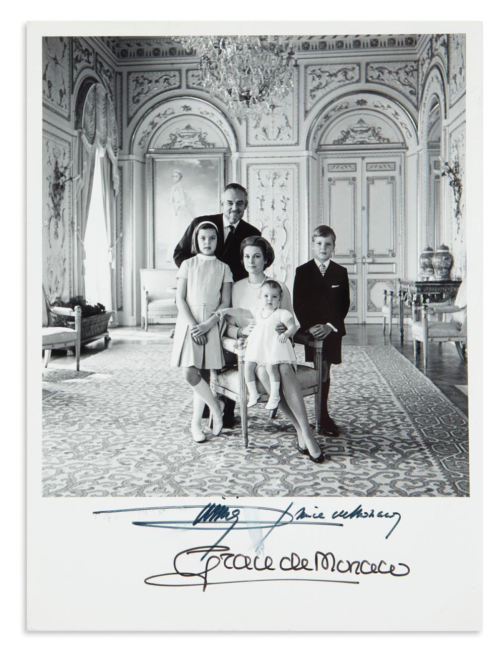 "GRACE; PRINCESS OF MONACO. Group Photograph Signed, ""Grace de Monaco,"" full-length portrait showing her seated and surrounded by her hu"