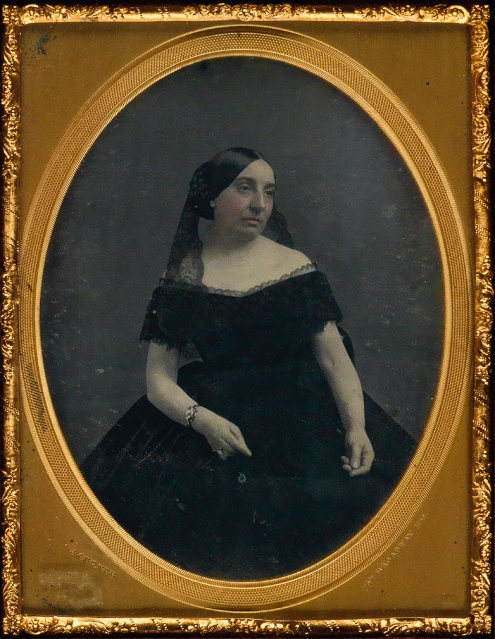 JEREMIAH GURNEY (1812-1895) A lightly-tinted half-plate daguerreotype portrait of a woman in a lace trimmed off-the-shoulder dress.
