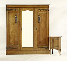 An Arts and Crafts oak triple wardrobe, inset with