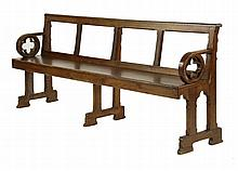 An oak 'Gothic' hall bench, with a pierced back,