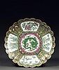 GRAND PLAT en porcelaine, émaux polychromes dans le style de la famille rose et dorure, le bord festonné, à décor, sur le bassin, d'...
