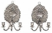 PAIRE DE PETITES APPLIQUES MURALES à trois bras de lumière. La plaque de support en argent est ornée de deux angelots dans un décor...