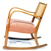 FRITZ HANSEN (ÉDITEUR) A rocking-chair with frame of stained beech, back with rattan cane