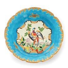 LONGWY Coupe en faïence sur piédouche, à décor d''oiseau en émaux cloisonnés polychromes sur fond bleu et blanc, rehauts or