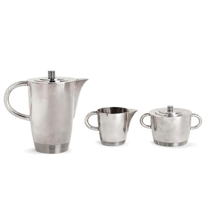 LURELLE GUILD (1898-1986) Service à thé en métal argenté, décor partiel de rainures, comprenant une verseuse et son couvercle, un su...