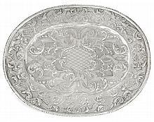 PLAT OVALE en argent, à décor au repoussé de rinceaux et ornements feuillagés sur fond amati, orné au centre d'un cartouche ciselé d...