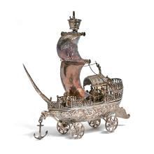 NERESHEIMER & SÖHNE - HANAU (DÉBUT XXE) Nef en argent, posant sur quatre roues, la coque à décor au repoussé de scènes mythologiqu...