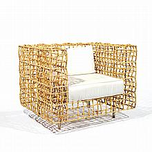 ANNÉES 80Fauteuil à structure cubique formée d''une résille en osier, piétement cylindrique en métal reposant sur des patins en caout...