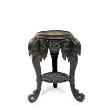 ANNÉES 1880 Sellette en bois noirci, piétement tripode aux têtes d''éléphant, tablette inférieure et lambrequins en ceinture à décor...